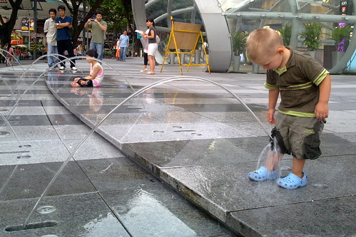 Boy playing with fountain outside Ion