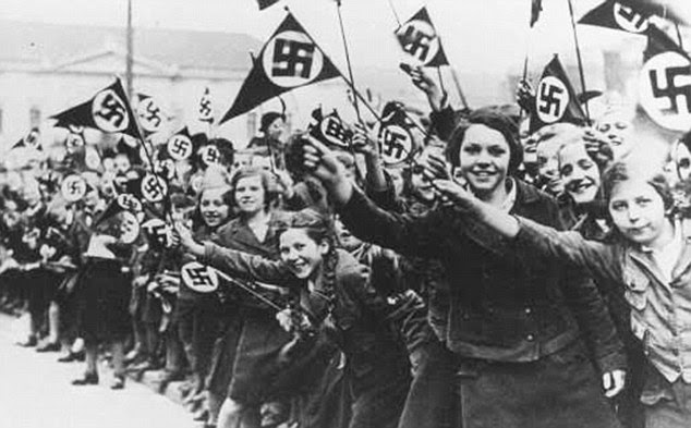 Chilling: Schoolchildren wave flags emblazoned with Swastikas