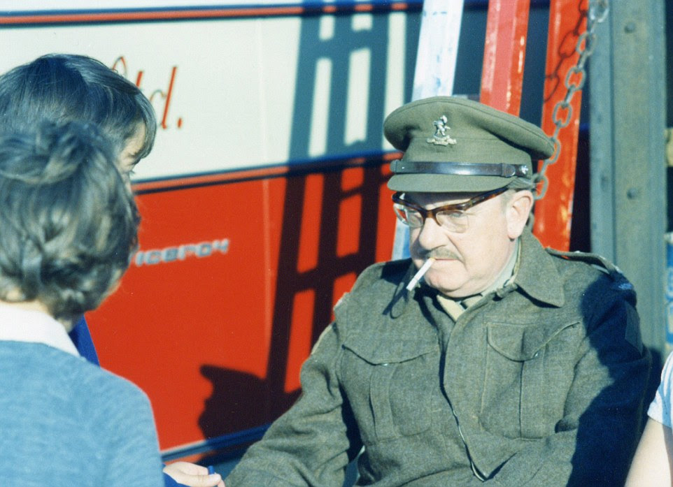 Arthur Lowe, in full Captain Mainwaring uniform but with a cigarette dangling uncharacteristically from his lips, signs his name for two young autograph hunters