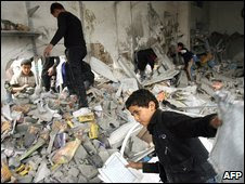 Palestinian children search the ruins of a destroyed house following an Israeli air strike in the northern Gaza Strip, 29 December 2008