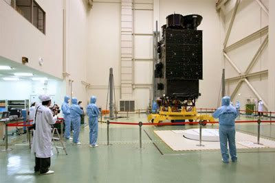Technicians gaze at the SELENE spacecraft in a processing facility in Japan.