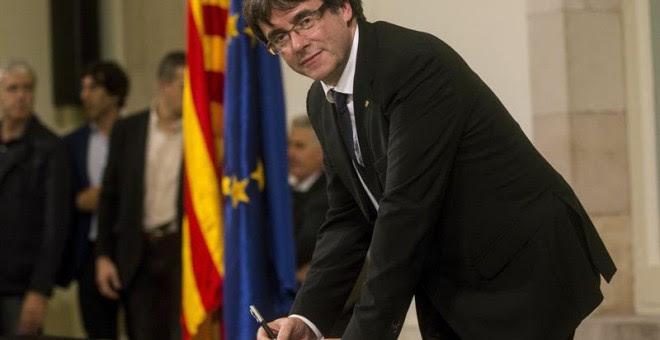 Puigdemont firma el documento de adhesión a la República catalana después de comparecer ante el pleno del Parlament para trasladar los resultados de la jornada del 1-O. | QUIQUE GARCÍA (EFE)