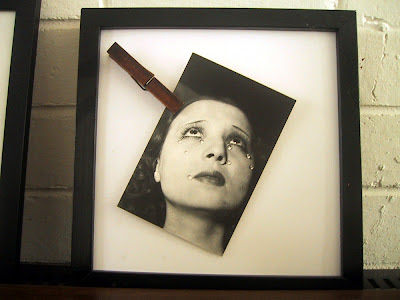 Glass-less picture frame containing a Man Ray postcard held in place by a clothes peg.