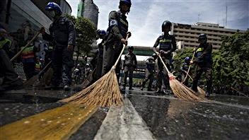 Des policiers nettoient le site où une bombe a explosé au centre de Bangkok
