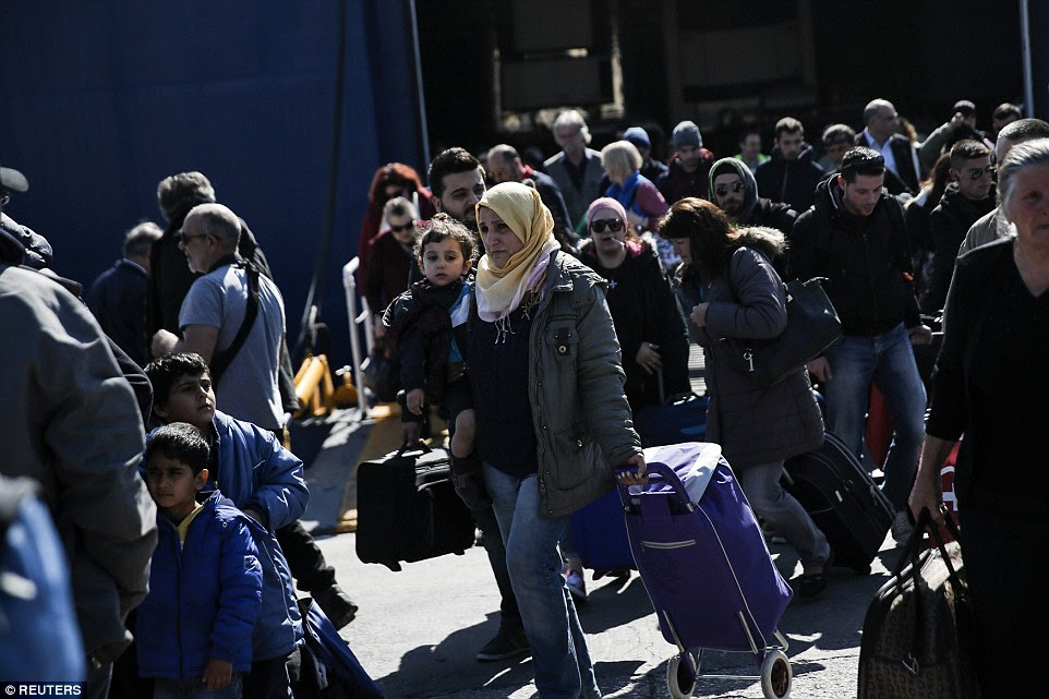 Refugees and migrants arrive aboard the Diagoras passenger ship at the port of Piraeus, near Athens, Greece