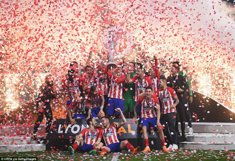 Torres lifts the Europa League trophy for Atletico as the players celebrate their victory on Wednesday night in Lyon