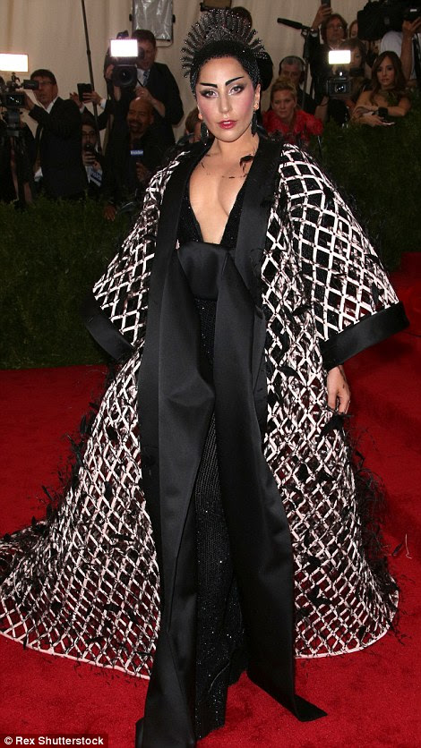 A severe look: Lady Gaga teamed a netted custom Alexander Wang for Balenciaga black and white robe with a headdress, sparkly platforms, and extreme eyebrows