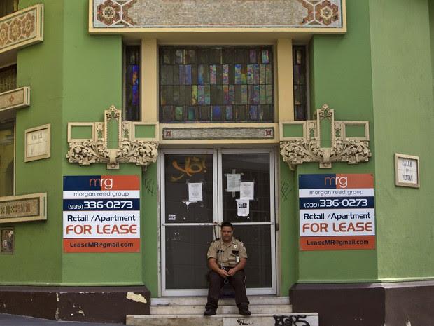 Imagem de domingo (2) mostra guarda sentado em frente a uma loja fechada na capital San Juan, em Porto Rico  (Foto: AP)