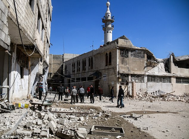 People inspect the Great Mosque, damaged during the Assad regime's airstrike, in Arbin town in Damascus, Syria