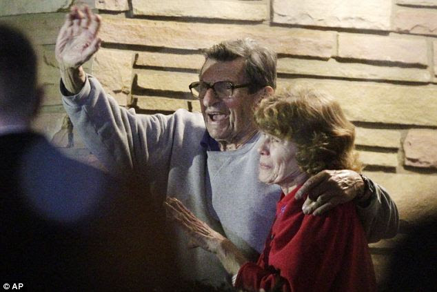 Waving to the crowd: Joe Paterno and his, wife, Susan, stand on their porch to thank supporters gathered outside their home after the football coach was sacked