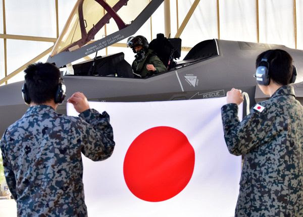 At Luke Air Force Base in Arizona, Japan Air Self-Defense Force (JASDF) pilot Lt. Col. Nakano sits inside the cockpit of an F-35A Lightning II as JASDF maintainers display a Japanese flag...on February 7, 2017.
