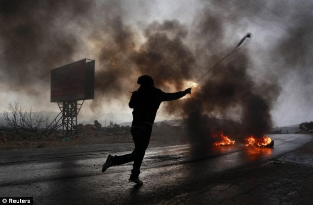 A Palestinian man uses a sling to hurl a stone during clashes with Israeli troops at a protest in the West Bank