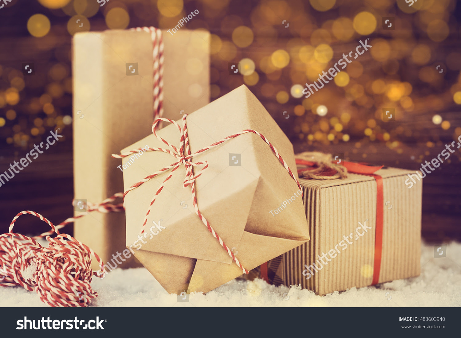 http://www.shutterstock.com/pic-483603940/stock-photo-christmas-gift-boxes-wrapped-in-brown-paper-with-red-ribbon-on-golden-bokeh-background-in-vintage-style-shallow-focus.html