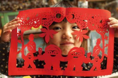 大紅色紙、主角手舞足蹈,剪紙裡的每處細節都有楊士毅 想帶給人的歡喜和溫暖。(楊士毅提供)