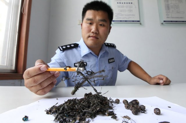 Theft: A policeman holds up some of the items from the grave which Mr Miao stole and shared out between his friends