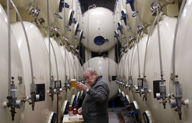 In this Tuesday, Oct. 30, 2012 photo, a brewer checks a glass of beer at the Budejovicky Budvar brewery in Ceske Budejovice, Czech Republic. They've been arguing about a name for 106 years. A small brewer in the Czech Republic and the world's biggest beer maker have been suing each other over the right to put the word Budweiser on their bottles in what has become a David versus Goliath corporate saga. A deal, it seems, will have to wait a bit longer because settlement talks between state-owned Budejovicky Budvar and Anheuser-Busch, a U.S. company now part of AB InBev, have collapsed, according to Budvar's director general, Jiri Bocek. (AP Photo/Petr David Josek)