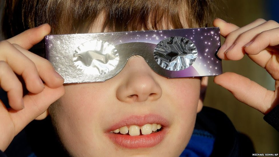 A boy poses for a photograph and looks up to the sun wearing protective goggles in Berlin, Germany
