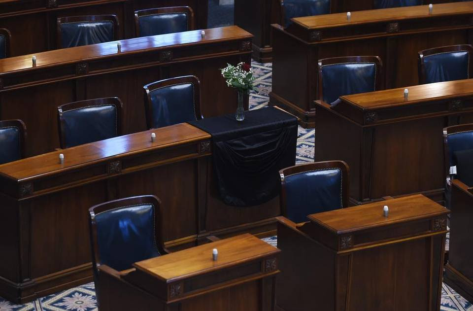 The desk of S.C. Sen. Clementa Pinckney is draped in black cloth with a single rose and vase in an empty chamber prior to a Senate session, Thursday, June 18, 2015, at the Statehouse in Columbia, S.C. Pinckney was killed, Wednesday, June 17, 2015, in a shooting at an historic black church in Charleston, S.C. (AP Photo/Rainier Ehrhardt)