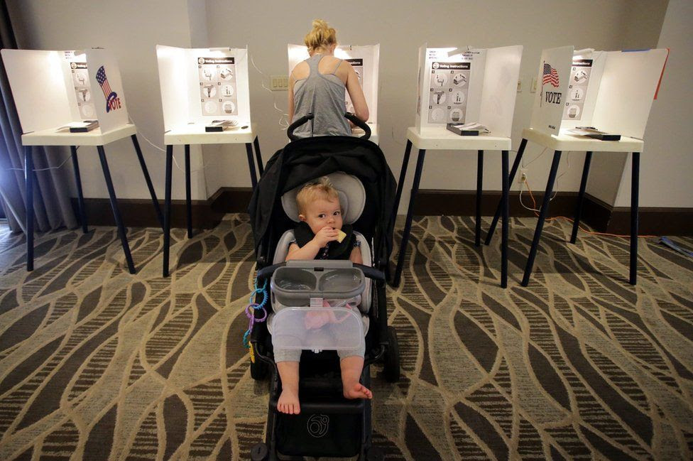 Lucille Lemkin waits in her stroller as her mother casts her ballot at the Luxe Hotel, California