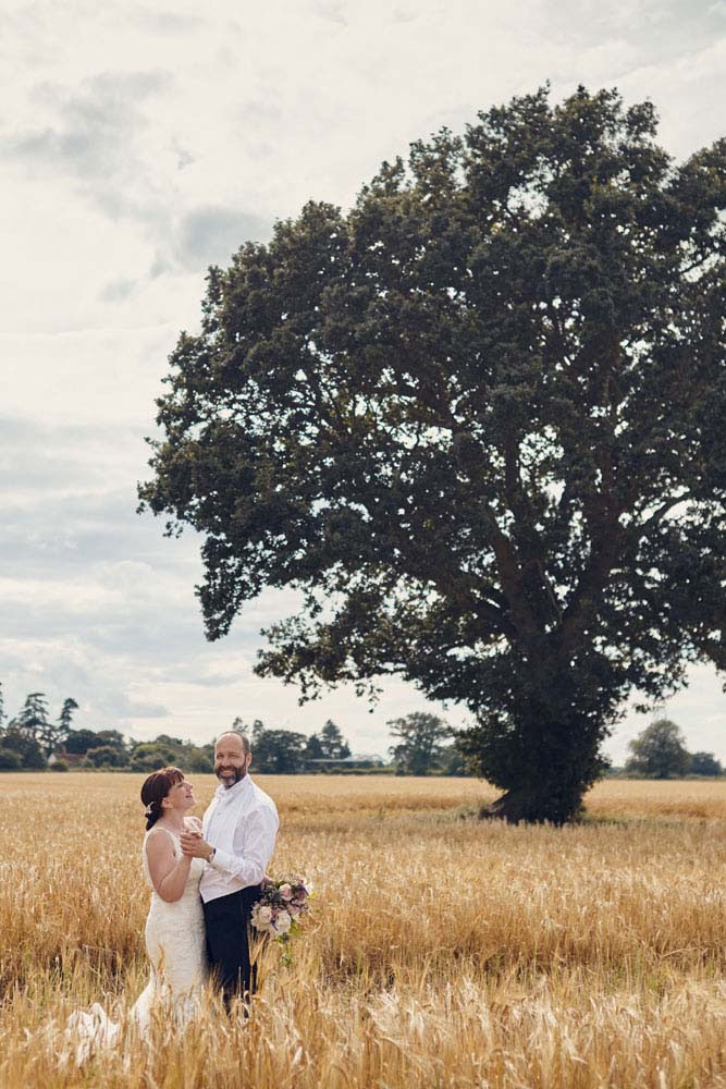 bride and groom in long grass in field with tree - www.helloromance.co.uk