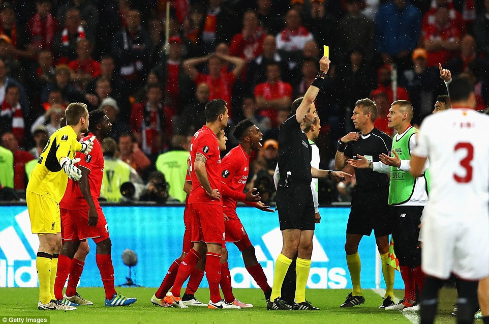 Liverpool substitute Skrtel (right) is shown a yellow card after protesting that Sevilla's third goal was offside