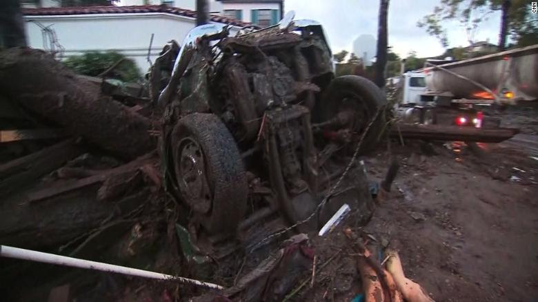 The remains of a car are jammed against muddy debris Tuesday in Montecito in Santa Barbara County.