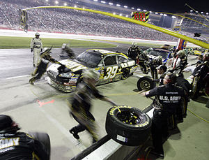 The Army team changes tires on the #39 Chevy I...