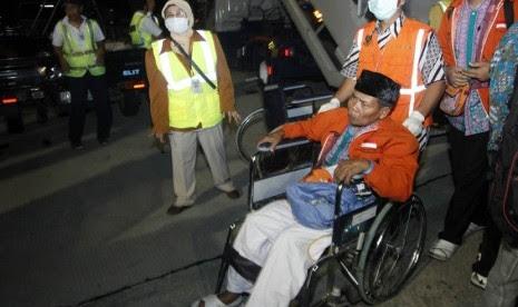 Jamaah Haji Kloter pertama Debarkasi Surakarta asal Kabupaten Sukoharjo yang sakit menggunakan bantuan kursi roda menuju mobil ambulans setibanya di Bandara Adi Sumarmo, Boyolali, Jawa Tengah, Kamis (1/11) dinihari.   (Herka Yanis Pangaribowo/Antara)