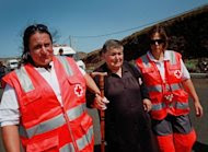 Red Cross members help a neighbor of the small town of La Restinga to walk towards a soccer field as a precaution against another possible undersea volcanic eruption, on October 11. Two new volcanic eruptions were confirmed on Wednesday near Spain's El Hierro island in the Canaries, where 500 people spent another night outside their homes after being evacuated as a precautionary measure