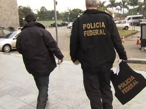 Policiais federais com malotes apreendidos na Operação Boca Livre (Foto: Reprodução/TV Globo)