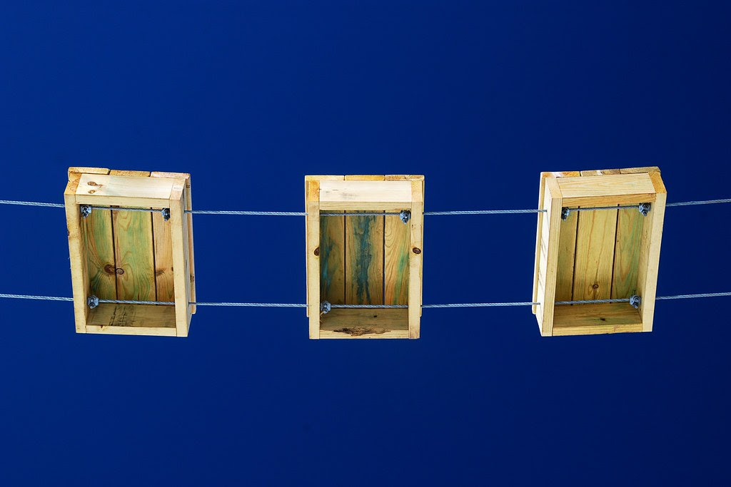 Yellow wooden blocks hanging on wires, against a deep blue sky.