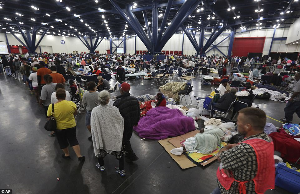 People line up for food at the George R. Brown Convention Center in Texas on Tuesday morning after spending the night. There are 17,000 people at shelters across Texas and more are expected to need cover in the coming days