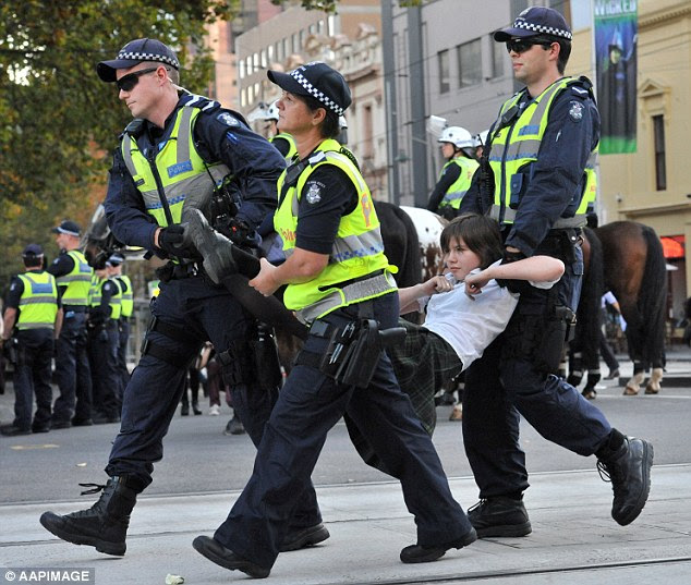 On for young and old: A girl in a school uniform was carried away from the crowd by police in Melbourne