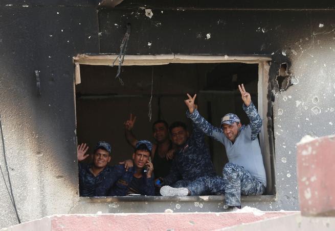 Des policiers irakiens font le V de la victoire durant les combats dans la vieille ville, qu'ils espèrent reprendre à l'Etat islamique d'ici la fin de la semaine.