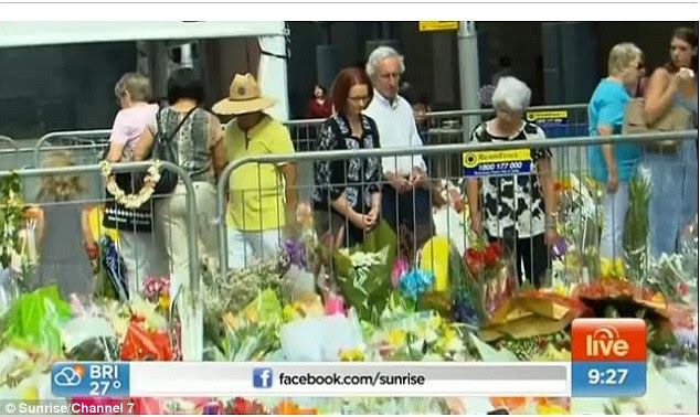 Ms Gillard paused after placing her tribute and walked around the memorial site