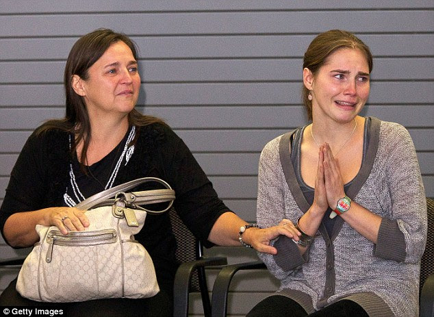 Amanda Knox (right) acknowledges the cheers of supporters while her mother Edda Mellas comforts her on her return home to Seattle, Washington, in October 2011 after winning an appeal against her conviction