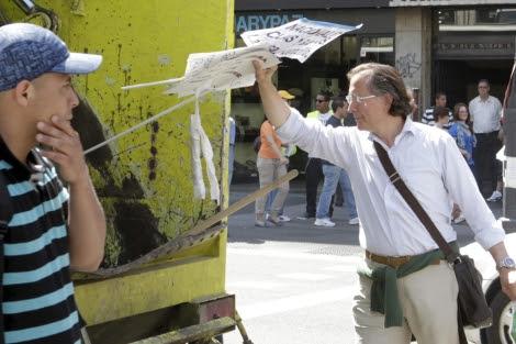 El hombre tirando varios carteles a la basura. | Efe