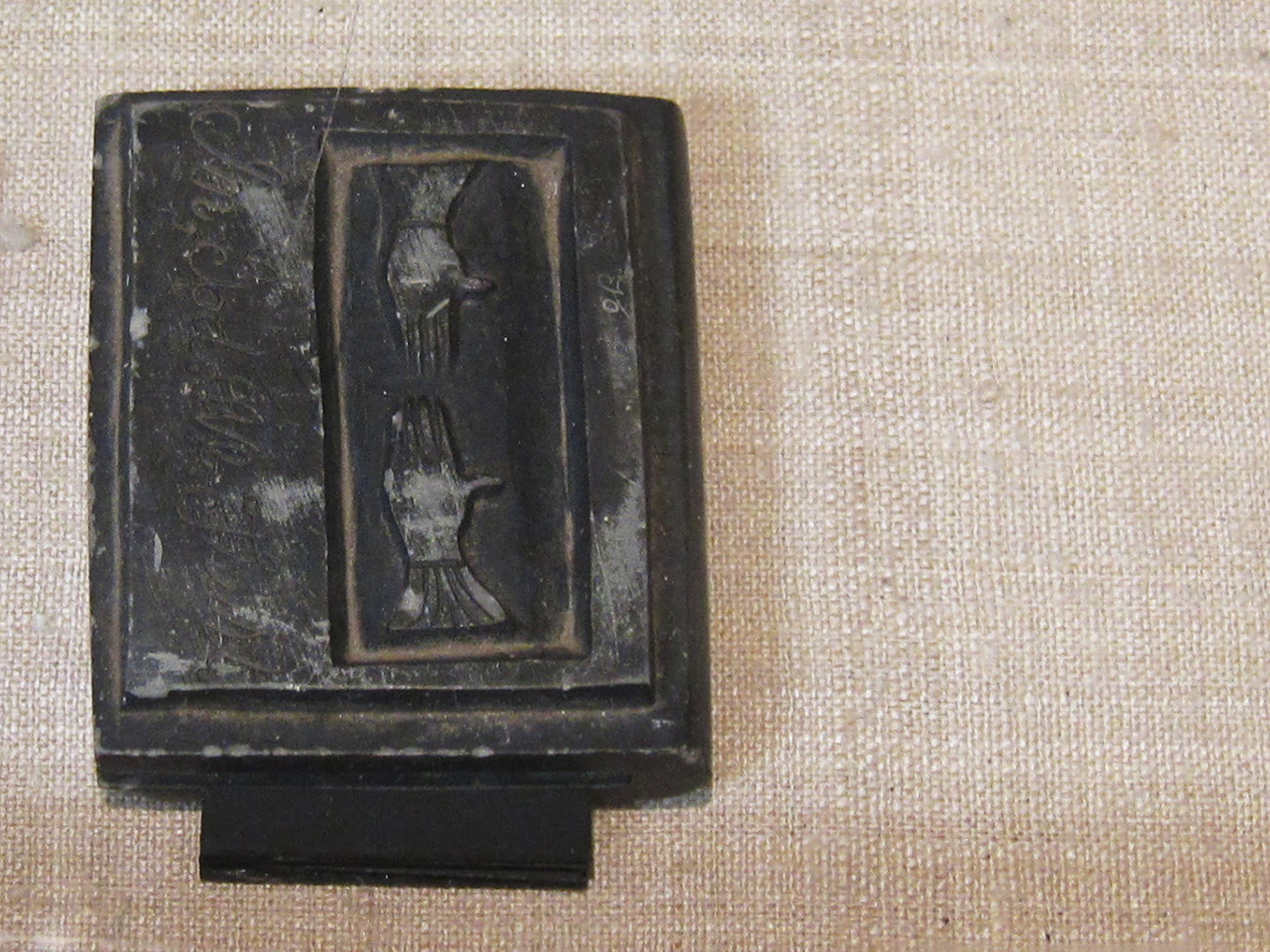 """Hand-carved slate memorial book, inscribed with """"In Memory"""" on the spine and """"In, God. We, Trust"""" on the cover"""