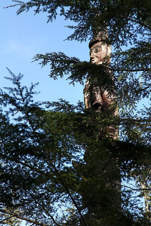 totem face through trees, Totems Historic District, Kasaan, Alaska
