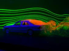 The orange liquid behind the car illustrates the wake, which can  be used to determine drag for the car. The green lines across illustrate  the air moving across the car