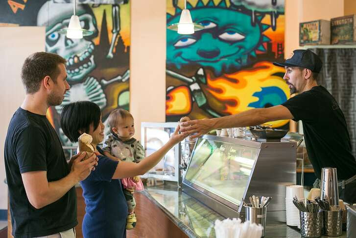 Jeffery Mann, Shakedown's co-owner, hands a scoop of ice cream to Faith Donal inside the birghtly colored ice cream shop.