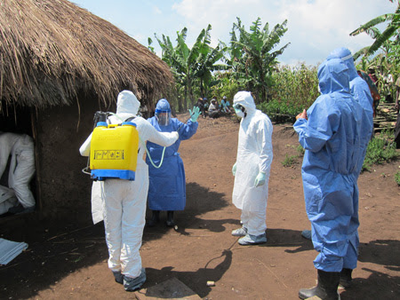 Health care workers dressed in protective clothing in an African village