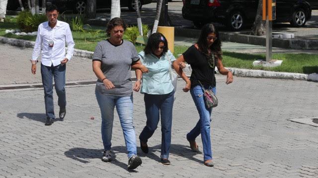 Denise (de blusa verde clara e faixa na cabeça) chega à Cidade da Polícia