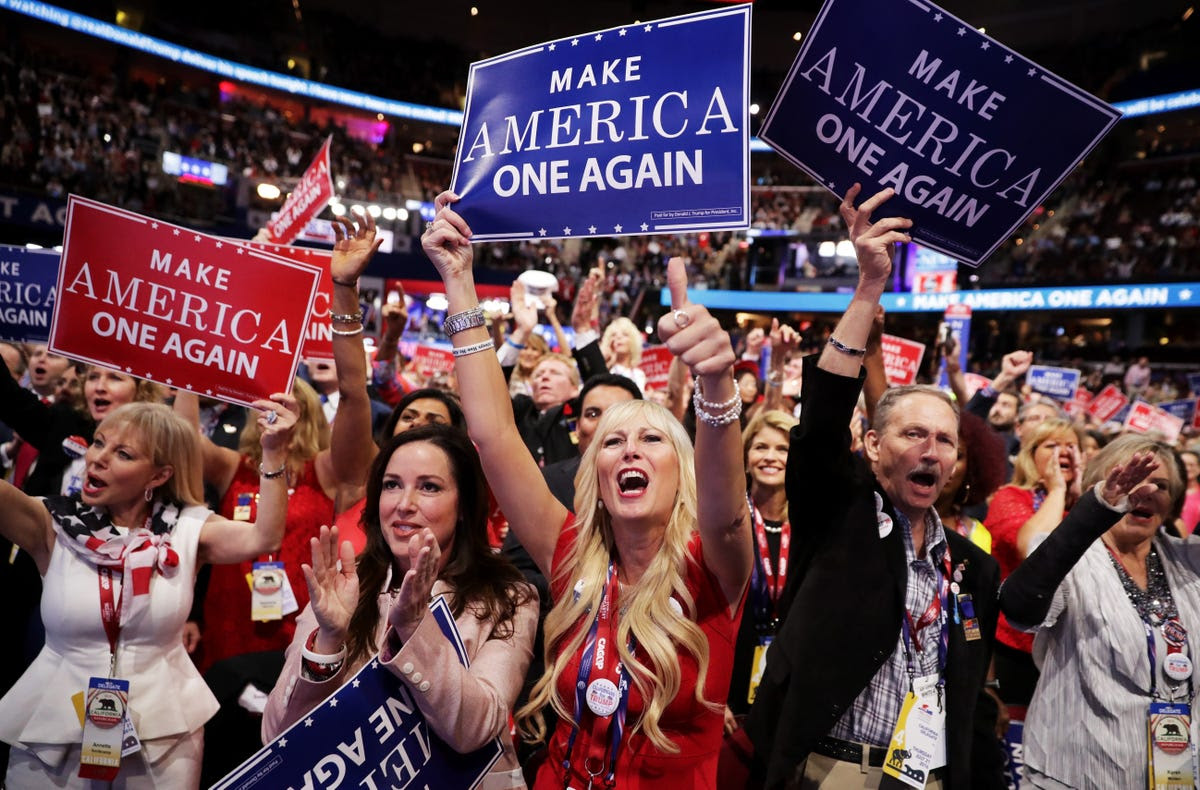 Delegates who are holding up signs that read 'Make America One Again' cheer on Trump's big night