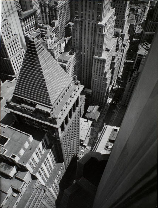 Wall Street, from roof of Irving Trust Co. Building, Manhattan. Looking down on edge of Irving Trust Bldg., pyramidal roof of building across street and Customs House, most of immage mass of buildings.