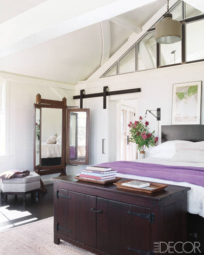 The light-filled master bedroom of Meg Ryan's home on Martha's Vineyard is all about ease. Vintage linens, simple lighting, and a barnstyle sliding door create a rustic feel. The custom-made bed and trunk were designed by Marsha Russell of Satinwood and made by Herrick & White , and the sconce is by O'Lampia Studio. Tour this house.