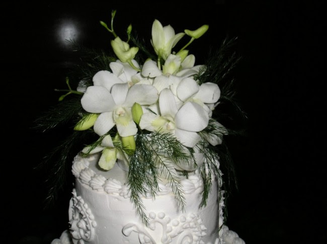 Here is the top of a white wedding cake that has white dendrobium orchids