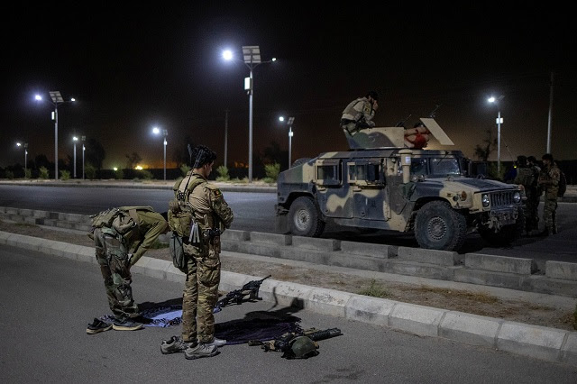 Members of the Afghan Special Forces pray on a highway before a combat mission against Taliban, in Kandahar province. Image courtesy: Danish Siddiqui/Reuters