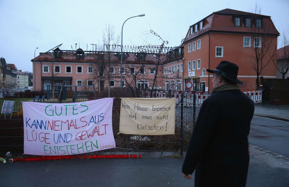 Un hombre ante carteles de protesta contra el incendio de un hotel, este lunes en Bautzen (Alemania).