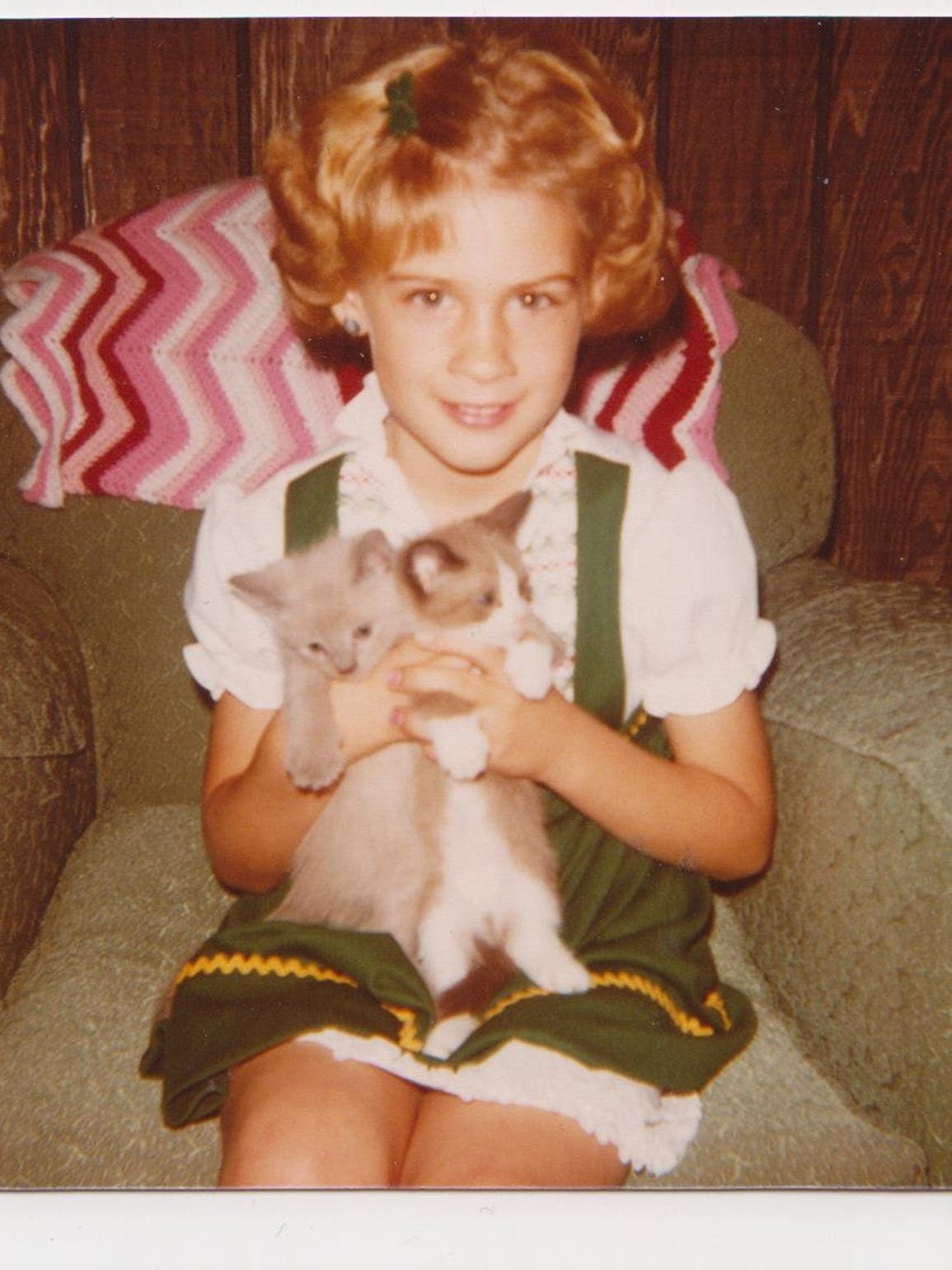 Heidi Wolfe poses for a picture with two kittens. Year